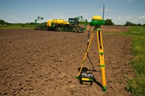Starfire RTK receiver in front of a John Deere tractor with tiller in a field