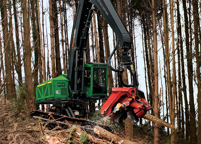 909MH Tracked Harvester with Waratah attachment cutting into a tree at a job site