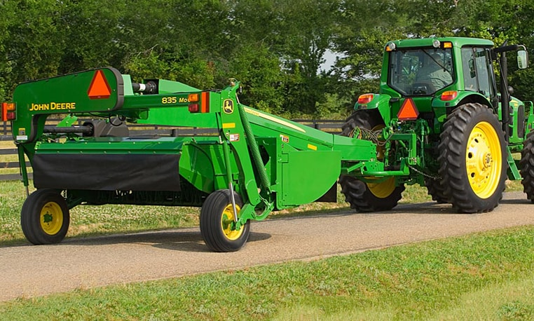 A John Deere tractor pulls an 835 Mower Conditioner down a path