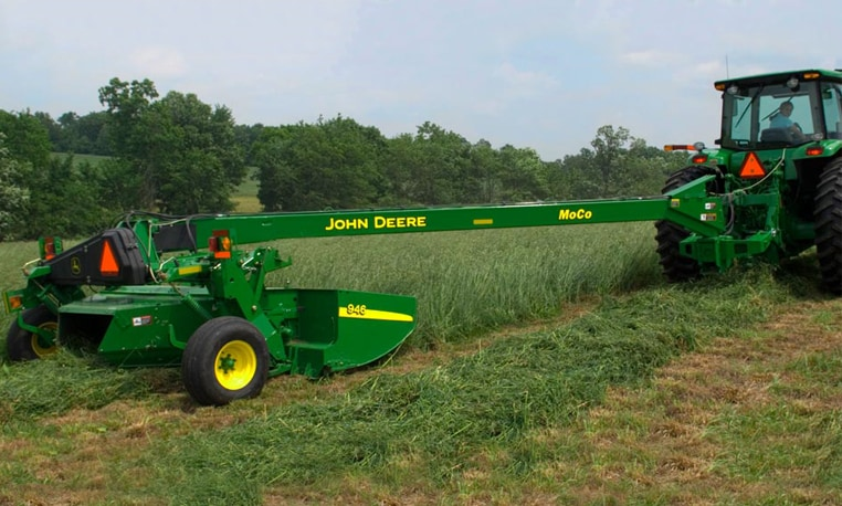 An 835 Mower-Conditioner is pulled behind a John Deere tractor