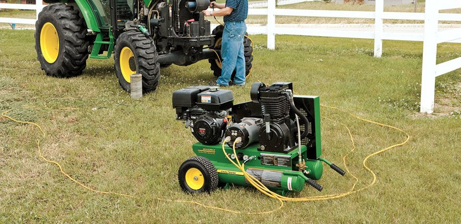 John Deere Compresserator™ on a lawn with a man working on John Deere Tractor in the background