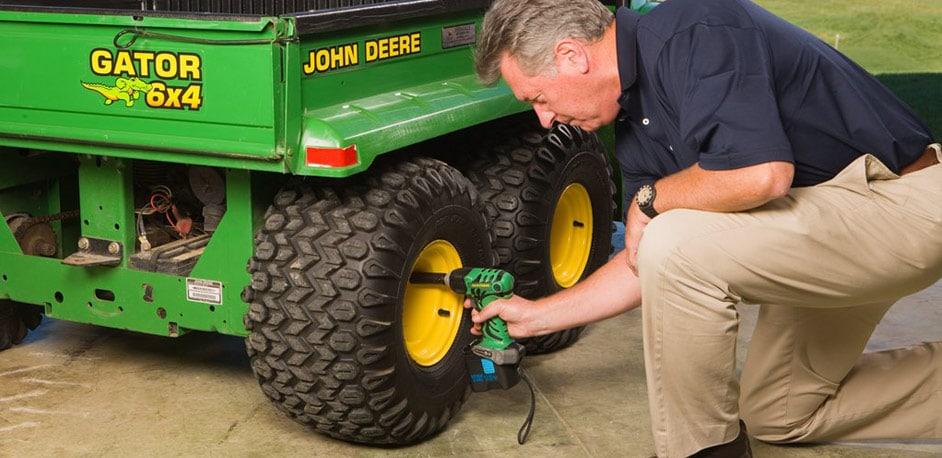 Man using a John Deere Power Tool to fix a tire on a Gator