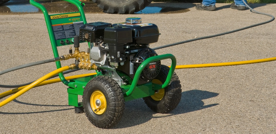 John Deere Pressure Washer on a driveway with man's feet and tractor tire in the background