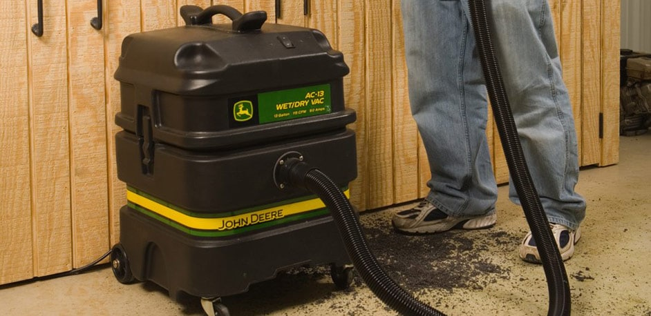 Man using a John Deere Wet/Dry Vacuum to clean around a work bench