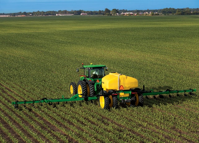 Overhead view of a John Deere tractor with 2510L Liquid Fertilizer Applicator in a field with blue sky in the background
