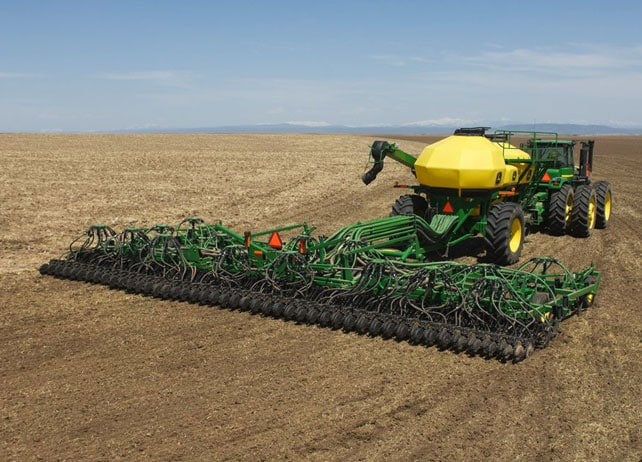 A rear view of the 730 Air Disk Drill being towed behind a John Deere tractor
