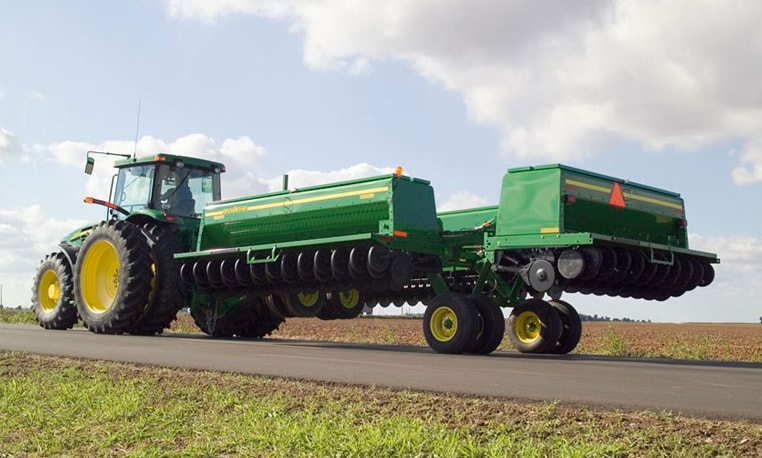 A collapsed Conventional-Till Drill is pulled behind a John Deere tractor for easy transportation