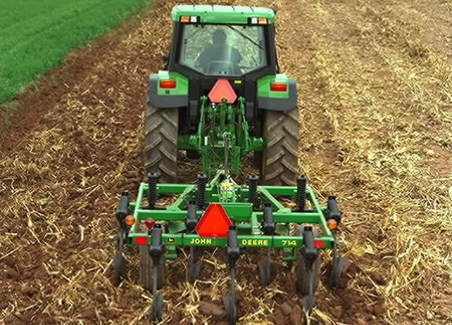 The 714 Mulch Tiller is pulled behind a John Deere tractor to till a field