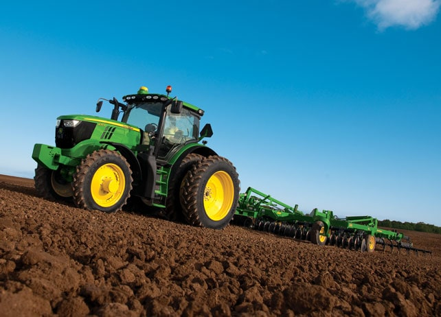 6210R Tractor rolls through a freshly plowed field against a deep blue sky