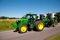 6R Series Tractor with attachment driving down a road