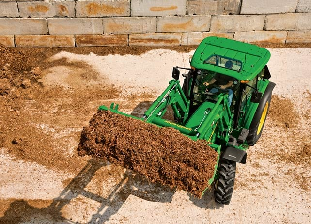 5100M Utility Tractor uses loader attachment to lift mulch