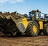 944K Hybrid Wheel Loader traveling with the bucket loaded with rock and dirt