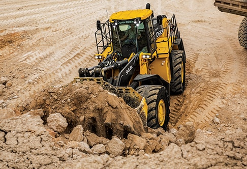 Front overhead view of the 944K Hybrid Wheel Loader scooping up rock and dirt