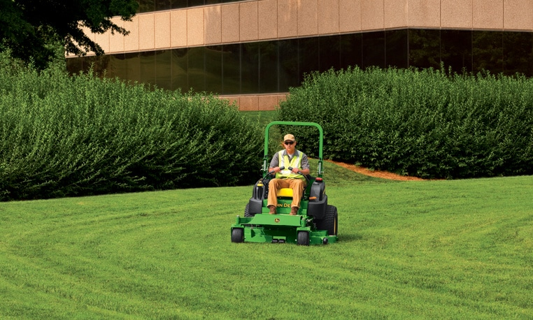 Landscape worker using a ZTrak 997 Diesel Series mower to trim the lawn of a commercial building