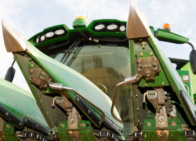 Closeup of a combine head harvesting corn in a field