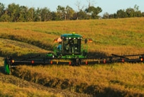 W155 Windrower moving through field