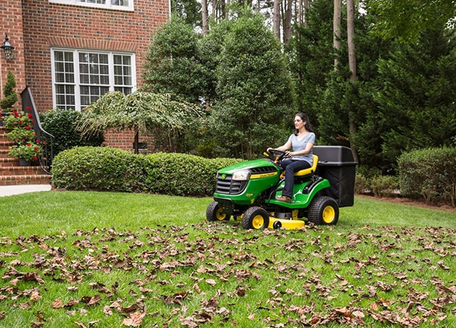 Woman driving D105 lawn tractor in residential property