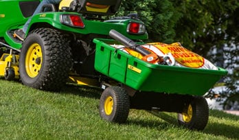 Cart being pulled behind a riding mower
