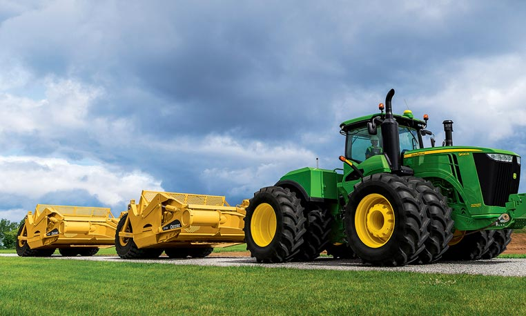 9R Series Scraper-Special Tractor driving down a road with a cloudy sky in the background
