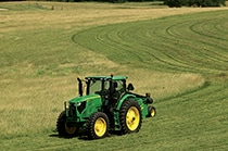 6175R tractor working in grassy field