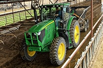 6195R Tractor spreading material in a farm building