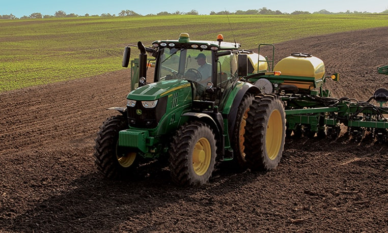 6R Series tractor with planter attachment working in a field
